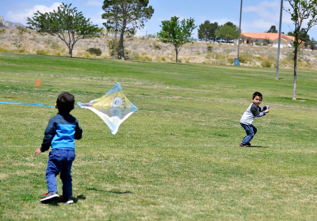Jadon Esperanza, left, helps launch a kite with his brother, Danile, while they attended a church picnic with their family at Lone Mountain Discovery Park on Sunday, May 11, 2014.  Gusty winds wil ...