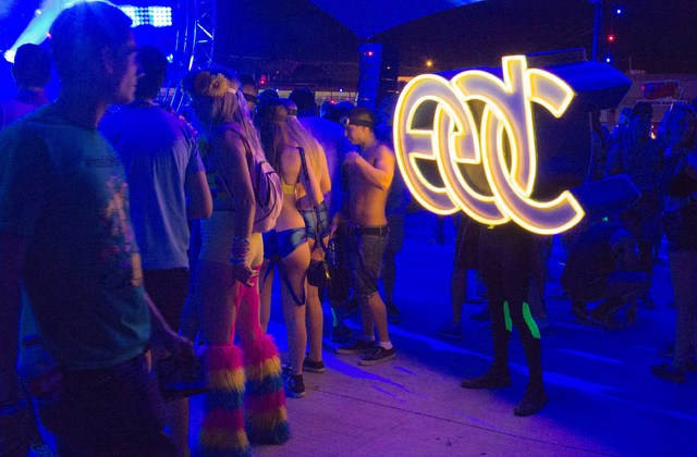 People dance with a man dressed as the EDC logo at the Electric Daisy Carnival on Saturday, June 21. (Kristen DeSilva/Las Vegas Review-Journal)
