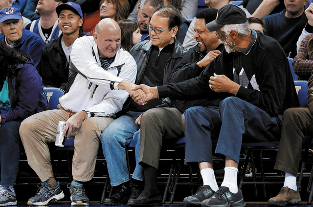 """In this Jan. 25, 2014, photo, then-Microsoft CEO Steve Ballmer, left, shakes hands with former NBA players Bill Russell, right, and """"Downtown"""" Freddie Brown as Omar Lee looks on during an NCAA col ..."""