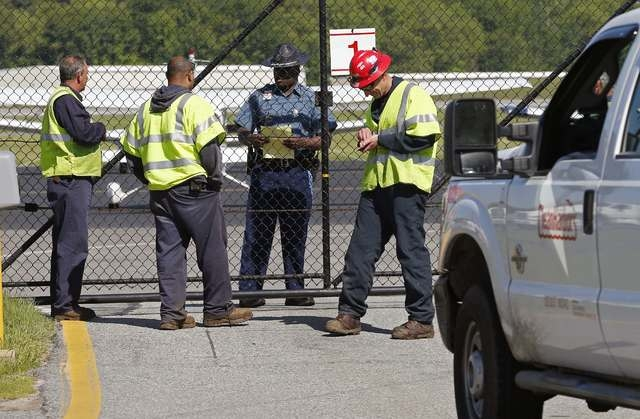 An environmental crew from Clean Harbors checks in before heading out to the site of a plane crash at Hanscom Field in Bedford, Mass., Sunday, June 1, 2014. A Gulfstream IV crashed as it was leavi ...