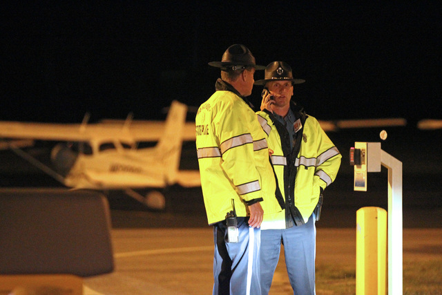 State Police stand at the gate of Hanscom Field where a private Gulfstream IV plane with seven people aboard crashed and caught fire late Saturday, May 31, 2014. (AP Photo/The Boston Herald, Stuar ...