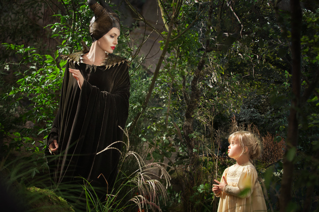 "This image released by Disney shows Angelina Jolie as Maleficent, left, in a scene with her daughter Vivienne Jolie-Pitt, portraying Young Aurora, in a scene from the film, ""Maleficent."" ..."