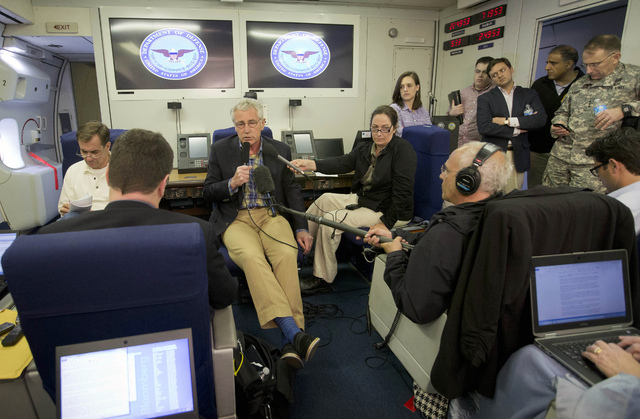 U.S. Defense Secretary Chuck Hagel, center, is seen aboard a U.S. Military Aircraft before speaking to members of the media during his flight, Sunday, June 1, 2014. Hagel spoke about the released  ...