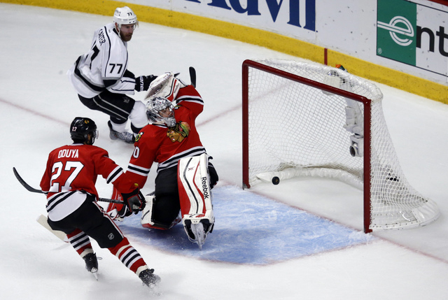 Los Angeles Kings center Jeff Carter (77) scores a goal against Chicago Blackhawks goalie Corey Crawford (50) as the Blackhawks defenseman Johnny Oduya (27) watches during the first period in Game ...