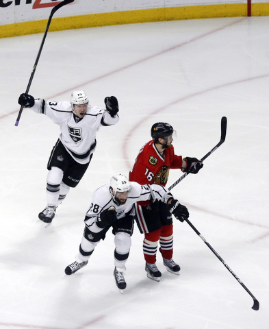 Los Angeles Kings center Tyler Toffoli, left, celebrates his game winning goal with center Jarret Stoll (28) as they pass Chicago Blackhawks center Marcus Kruger (16) during the overtime period in ...
