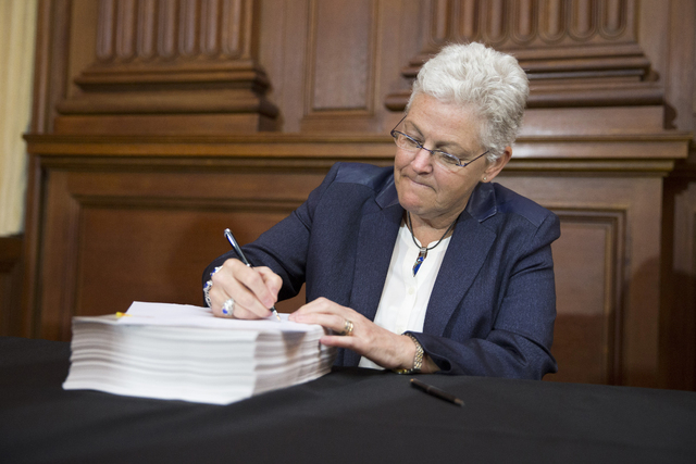 Environmental Protection Agency Administrator Gina McCarthy signs new emission guidelines during an announcement of a plan to cut carbon dioxide emissions from power plants by 30 percent by 2030,  ...