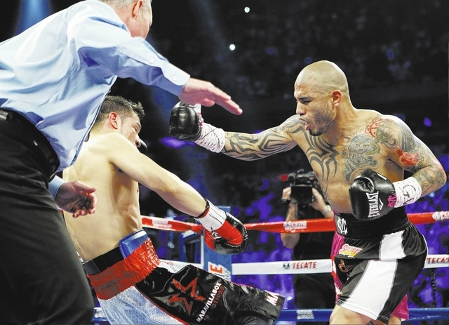 Miguel Cotto, of Puerto Rico, knocks down Sergio Martinez, of Argentina, during the first round of a WBC middleweight title boxing match Saturday, June 7, 2014, in New York. (AP Photo/Frank Frankl ...