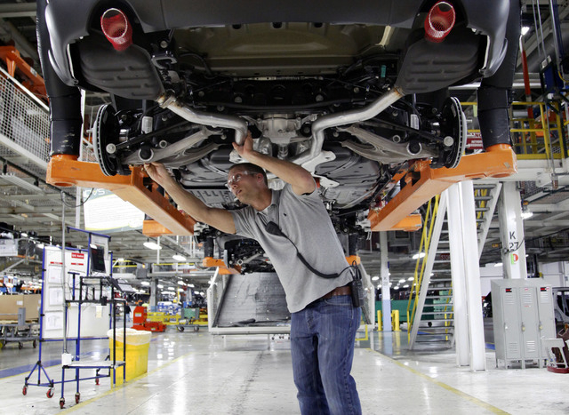 FILE - In this May 8, 2013 file photo, Jeff Caldwell, 29, a chassis assembly line supervisor, checks a vehicle on the assembly line at the Chrysler Jefferson North Assembly plant in Detroit. The U ...