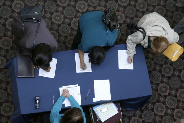 FILE - In this Jan. 22, 2014, file photo, job seekers sign in before meeting prospective employers during a career fair at a hotel in Dallas. The U.S. economy finally regained the jobs lost during ...