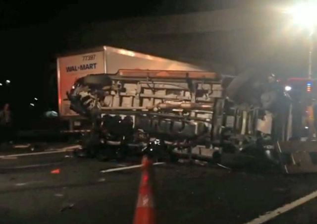 In this image from video the limousine bus carrying Tracy Morgan and six other people lies on it's side early Saturday morning June 7, 2014 on the New Jersey Turnpike. Morgan remained hospitalized ...