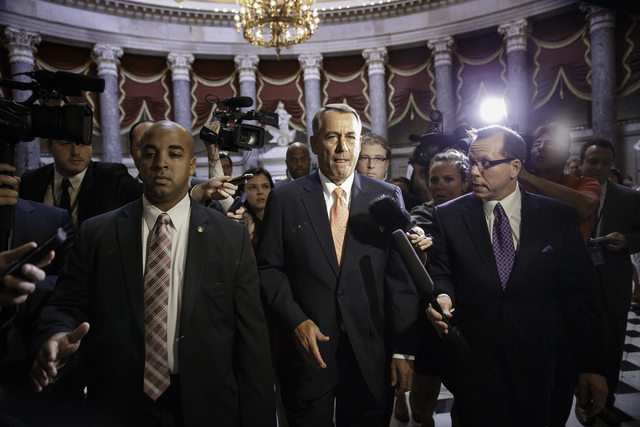 House Speaker John Boehner of Ohio is pursued by reporters as he walks from his office through the Capitol in Washington, Wednesday, June 11, 2014, the morning after the stunning political defeat  ...
