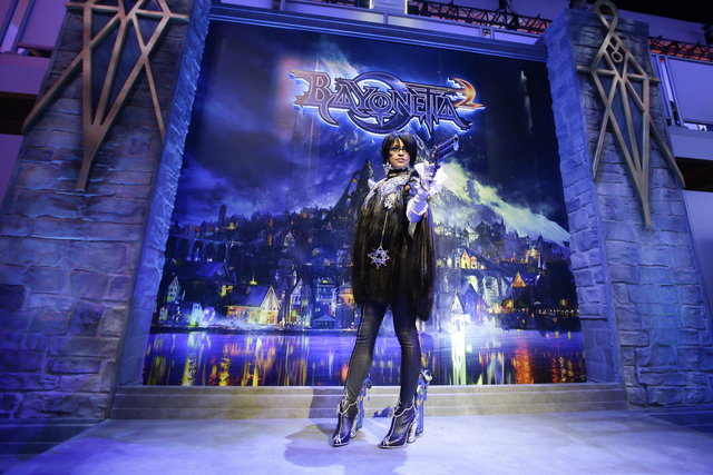 "FILE - In this June 12, 2013 file photo, a model dressed as Bayonetta, a video game character from the ""Bayonetta 2,"" poses for photos at the Nintendo booth during the Electronic Enterta ..."