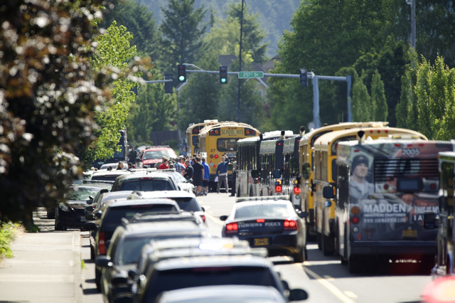 Students are led to waiting buses by police after a shooting at Reynolds High School in Troutdale, Ore., Tuesday, June, 10, 2014. A gunman killed a student at the high school east of Portland Tues ...