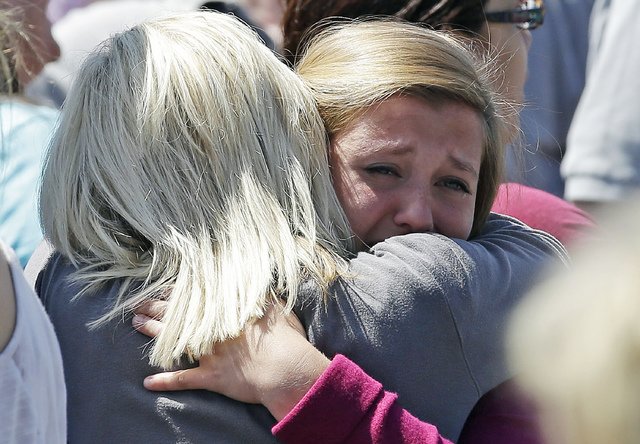 Freshman Hailee Siebert, 15, cries on her mother's shoulder after students arrived at a shopping center parking lot in Wood Village, Ore., after a shooting at Reynolds High School on Tuesday, June ...
