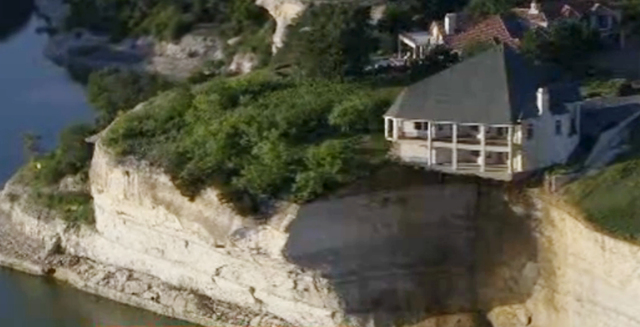 In this image taken from Tuesday, June 10, 2014 video provided by WFAA-TV, a luxury house teeters on a cliff about 75 feet above Lake Whitney in Whitney, Texas. WFAA-TV reported Wednesday, June 11 ...