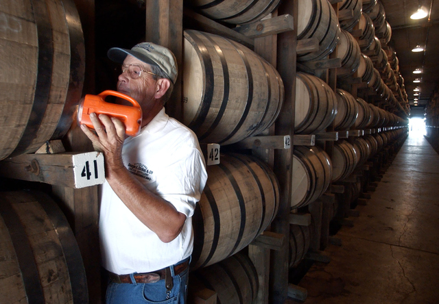 FILE -- In this Sept. 2003 file photo, Dewayne Evans checks for leaks in the barrels of whiskey aging in a warehouse at the George Dickel Distillery near Tullahoma, Tenn. Alcohol regulators ended  ...