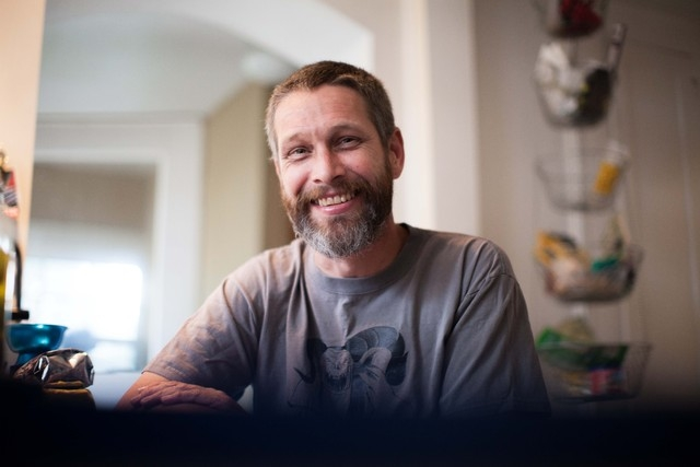 In this June 10, 2014 photo, Andy Hughes poses for a portrait in his home in Atlanta. A new study says men are more likely to get medical checkups if they're married rather than just living with a ...