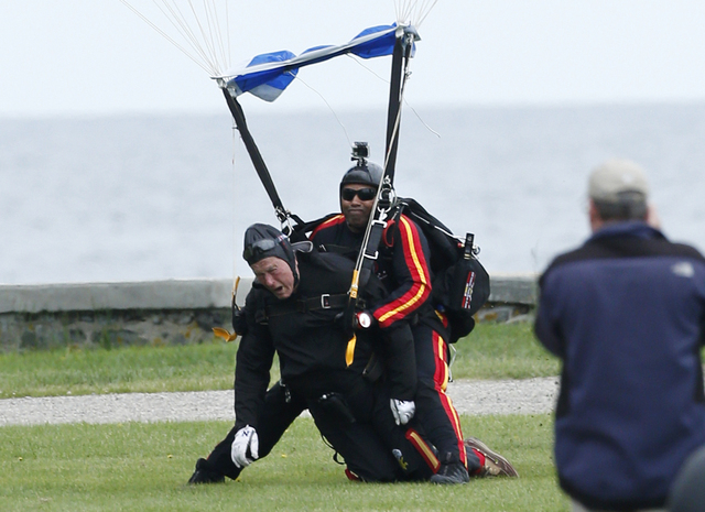 Former President George H.W. Bush, left, strapped to Sgt. 1st Class Mike Elliott, a retired member of the Army's Golden Knights parachute team, land on the lawn at St. Anne's Episcopal Church afte ...