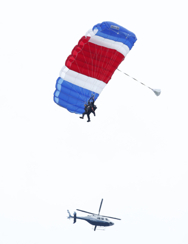 Former President George H.W. Bush, strapped to Sgt. 1st Class Mike Elliott, a retired member of the Army's Golden Knights parachute team, float to the ground during a tandem parachute jump near Bu ...