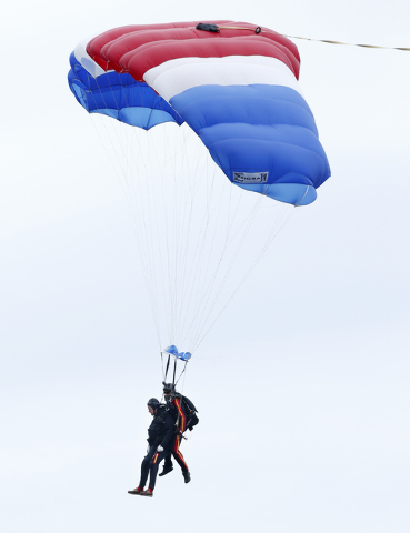 Former President George H.W. Bush, left, strapped to Sgt. 1st Class Mike Elliott, a retired member of the Army's Golden Knights parachute team, float to the ground during a tandem parachute jump n ...