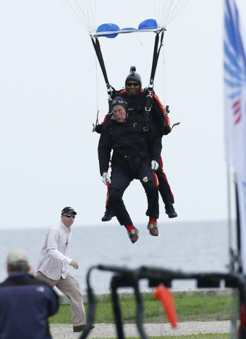 Former President George H.W. Bush, strapped to Sgt. 1st Class Mike Elliott, a retired member of the Army's Golden Knights parachute team, preapre to land on the lawn at St. Anne's Episcopal Church ...