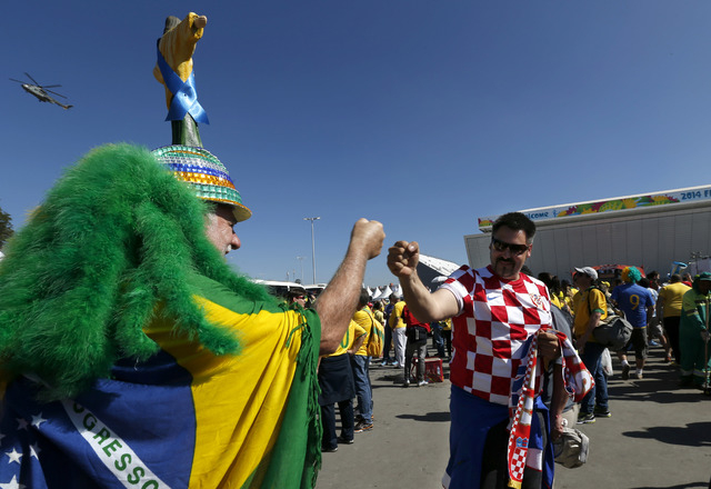 Brazilian soccer fan Amaceo Jgussi, left, fist bumps with Croatian fan Robert Krnezic, as they wait to enter the Itaquerao Stadium to watch the World Cup opening match, between Brazil and Croatia  ...