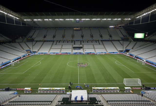 Croatia players gather in the center of the pitch during an official training session the day before the group A World Cup soccer match between Brazil and Croatia in the Itaquerao Stadium Sao Paul ...
