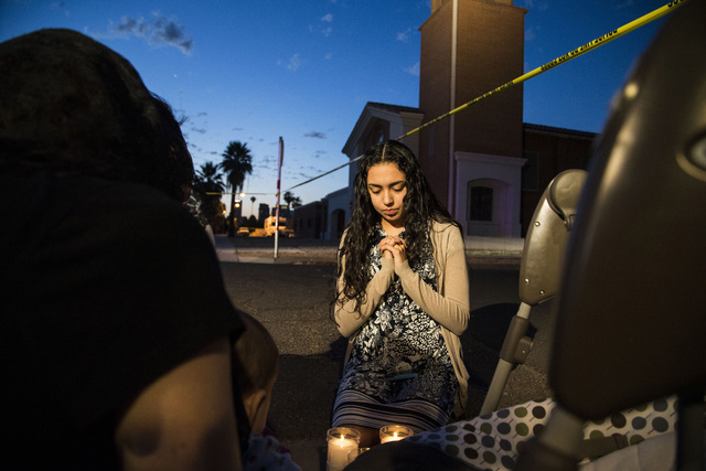 Mater Misericordiae (Mother of Mercy) Mission, church member, Kirsten Duarte, center, prays while Phoenix Police investigate a shooting at the church on Wednesday, June 11, 2014 in Phoenix. Police ...