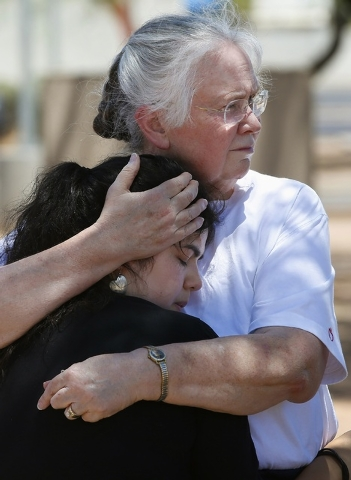 Marsha Livingston, right, comforts a grieving Kristen Williams, both parishioners at Mother of Mercy church, as they stand outside the church on Thursday, June 12, 2014, in Phoenix, after a Wednes ...