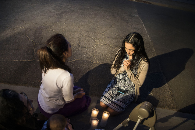 Mater Misericordiae (Mother of Mercy) Mission, church members Theresa Duarte, in center, and Kirsten Duarte, right, pray while Phoenix Police investigate a shooting at the church on Wednesday, Jun ...