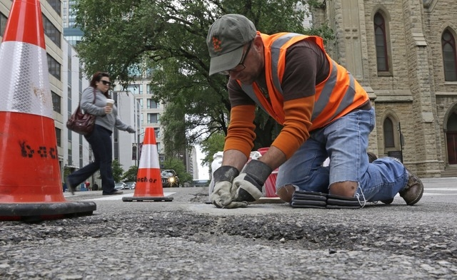 In this Tuesday, June 10, 2014 photo, mosaic artist Jim Bachor scrapes cement off a finished art piece on a street in Chicago. Bachor has filled seven potholes around the city and marks each one w ...