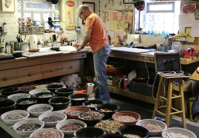 In this Monday, June 9, 2014 photo, Chicago mosaic artist Jim Bachor, looks over a checklist in his basement to make sure he has all the material he needs to complete a pothole art project. Bachor ...