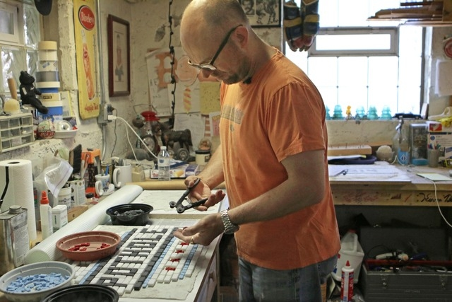 """In this Monday, June 9, 2014 photo, Chicago mosaic artist Jim Bachor works in his basement placing tiles on his next mosaic art piece that reads """"POTHOLES."""" Bachor has filled a few potholes around ..."""