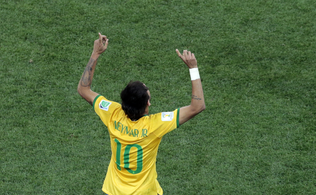 Brazil's Neymar celebrates scoring his side's first goal during the group A World Cup soccer match between Brazil and Croatia, the opening game of the tournament, in the Itaquerao Stadium in Sao P ...