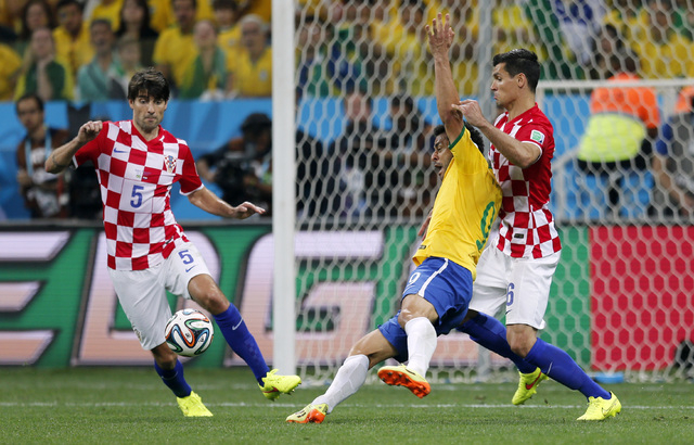 Brazil's Fred, center, falls next to Croatia's Dejan Lovren, right, as Croatia's Vedran Corluka, left, watches during the group A World Cup soccer match in the opening game of the tournament at It ...