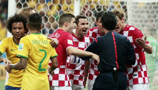 Croatia players argue with referee Yuichi Nishimura from Japan after being given a penalty during the group A World Cup soccer match between Brazil and Croatia, the opening game of the tournament, ...