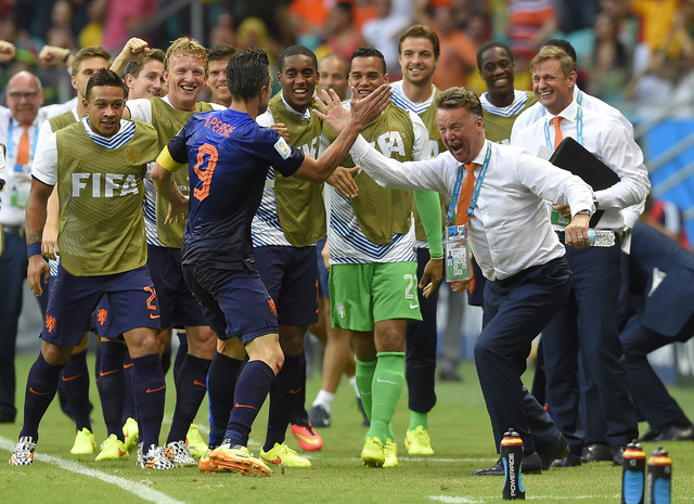 Netherlands' Robin van Persie celebrates with Netherlands' head coach Louis van Gaal after scoring a goal during the group B World Cup soccer match between Spain and the Netherlands at the Arena P ...