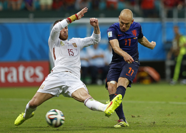 Netherlands' Arjen Robben kicks the ball past Spain's Sergio Ramos to score his side's second goal during the second half of the group B World Cup soccer match between Spain and the Netherlands at ...