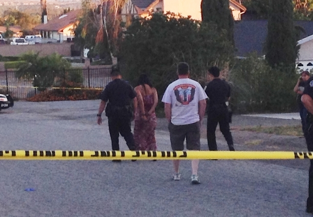 In this June 13, 2014 photo, authorities lead Soukvilay Barton away in handcuffs after she was arrested on suspicion of driving under the influence in Riverside, Calif. Riverside police Sgt. Dan R ...