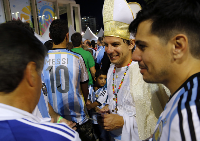 Argentina soccer fans, one dressed as Pope Francis, arrive to Maracana stadium for a World Cup soccer match with Bosnia in Rio de Janeiro, Brazil, Sunday, June 15, 2014. Argentina won the match 2- ...