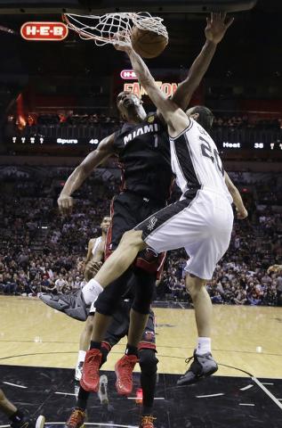 San Antonio Spurs guard Manu Ginobili (20) dunks over Miami Heat center Chris Bosh (1) during the first half in Game 5 of the NBA basketball finals on Sunday, June 15, 2014, in San Antonio. (AP Ph ...