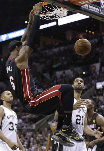 Miami Heat forward LeBron James (6) dunks as San Antonio Spurs forward Boris Diaw (33) and forward Tim Duncan (21) look on during the first half in Game 5 of the NBA basketball finals on Sunday, J ...