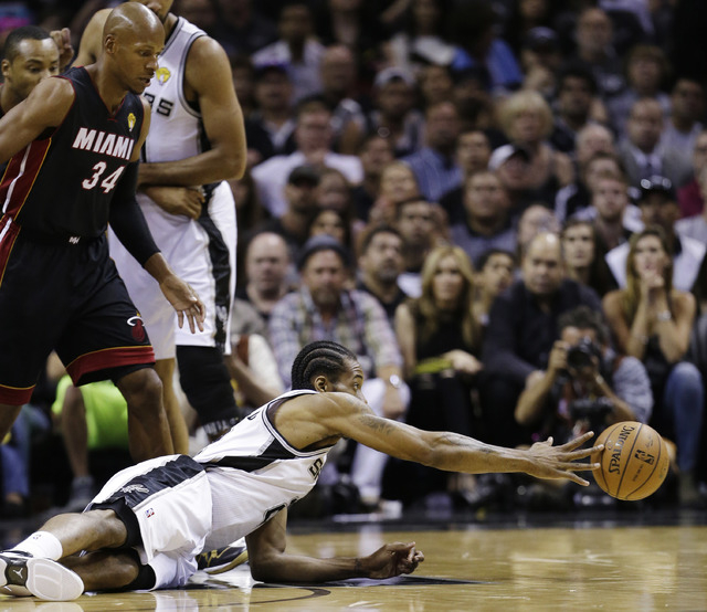 San Antonio Spurs forward Kawhi Leonard passes the ball after hitting the floor as Miami Heat guard Ray Allen (34) looks on during the first half in Game 5 of the NBA basketball finals on Sunday,  ...