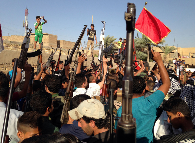 Shiite tribal fighters raise their weapons and chant slogans against the al-Qaida-inspired Islamic State of Iraq and the Levant (ISIL) in the east Baghdad neighborhood of Kamaliya, Iraq, Sunday, J ...