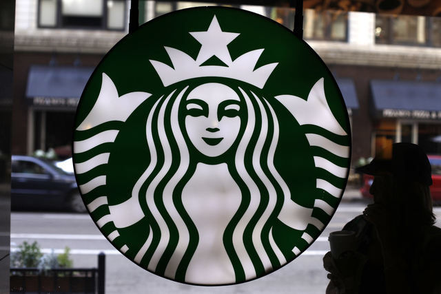 In this Saturday, May 31, 2014 photo, the Starbucks logo is seen at one of the company's coffee shops in downtown Chicago. Starbucks is announcing a new program to help its baristas earn an online ...