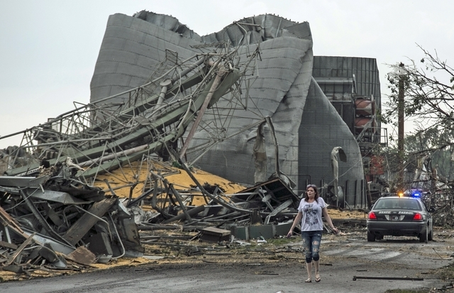A woman walks down Black Hills Trail road in Pilger, Neb., Monday, June 16, 2014. Two people were killed and at least 16 are in critical condition after two massive tornadoes swept through northea ...