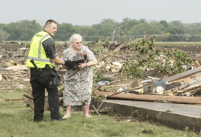Ruth Labenz is assisted to safety by a Stanton County Sherriff's officer after her home was destroyed in the town of Pilger, Neb. Monday, June 16, 2014. Two people were killed and several were inj ...