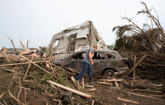 Tim Nelson searches for survivors in Pilger, Neb., after the town was hit by a tornado Monday June 16, 2014. Two people died in the storm. (AP Photo/The Omaha World-Herald/Ryan Soderlin)