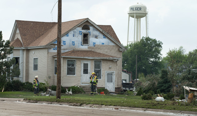 Firefighters go door to door and check homes for people after a tornado struck in Pilger, Neb., Monday, June 16, 2014. The National Weather Service said at least two twisters touched down within r ...