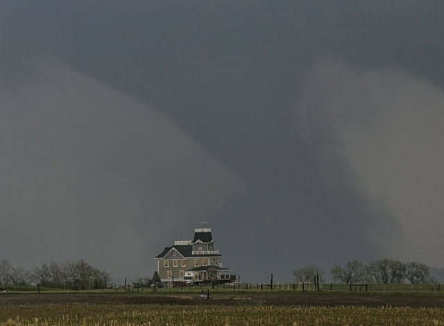 A tornado forms over a house near Pilger, Neb., Monday, June 16, 2014. At least one person is dead and at least 16 more are in critical condition after two massive tornadoes swept through northeas ...